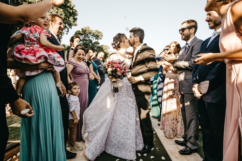 Newlywed couple sharing a kiss while surrounded by wedding guests